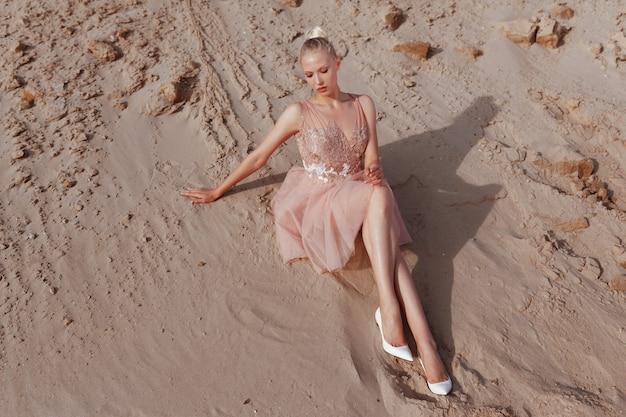 Aantrekkelijke blonde vrouw poseren in borduurjurk op woestijn, liggend op zand, bij de zonsondergang licht.