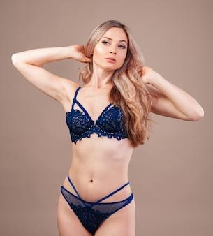 Aantrekkelijke blonde vrouw poseren in modieuze lingerie in studio