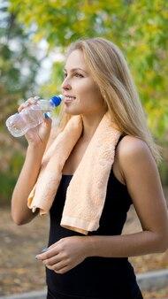 Aantrekkelijke blonde vrouwelijke atleet gebotteld water drinken voor hydratatie na het trainen in het park oefeningen te doen