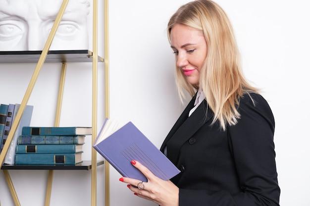 Aantrekkelijke blonde zakenvrouw in een pak staat bij de boekenplank en leest een boek