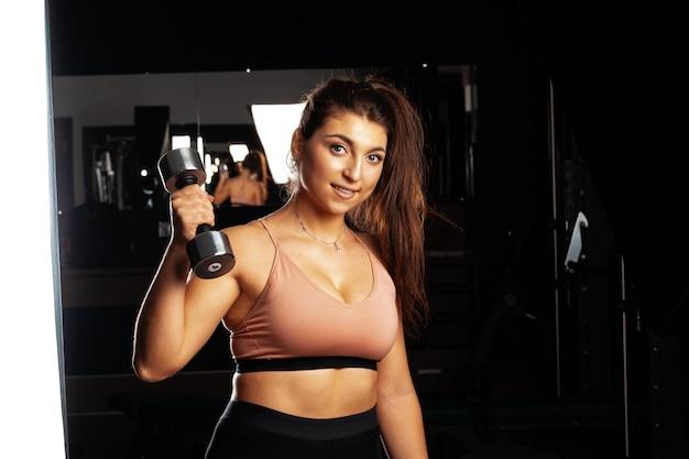 Aantrekkelijke bochtige jonge vrouw die met domoor in een gymnastiek uitwerkt, donkere achtergrond