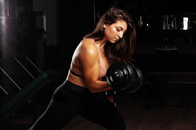 Aantrekkelijke bochtige jonge vrouw die met domoor in een gymnastiek uitwerkt