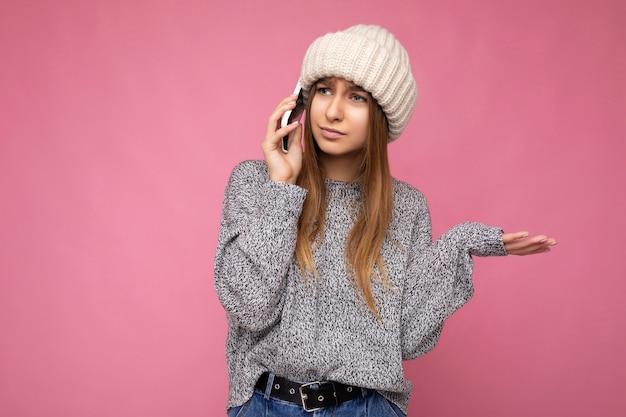 Aantrekkelijke boos jonge blonde vrouw, gekleed in casual grijze trui en beige hoed geïsoleerd over roze muur in de hand houden en praten op mobiele telefoon op zoek naar de kant en met vragen.