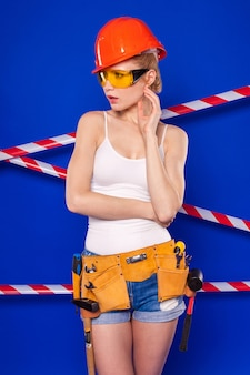 Aantrekkelijke bouwersvrouw in wit overhemd, bouwersriem, helm, bouwersglazen, korte broek en giechels