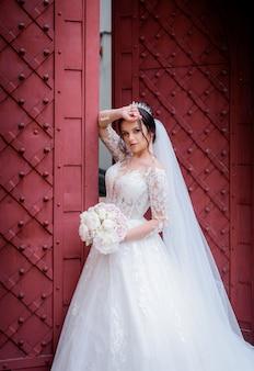 Aantrekkelijke bruid gekleed in luxe jurk in de buurt van de rode ingang