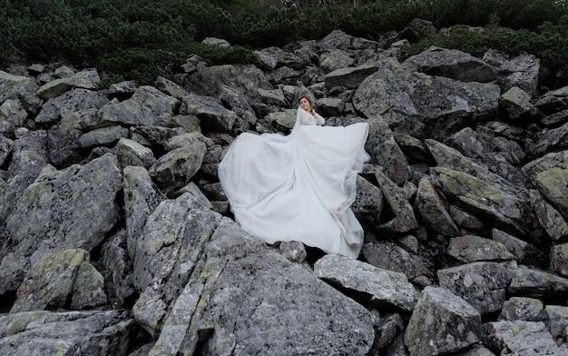 Aantrekkelijke bruid staat op de enorme grijze rotsen gekleed in witte ceremoniële jurk