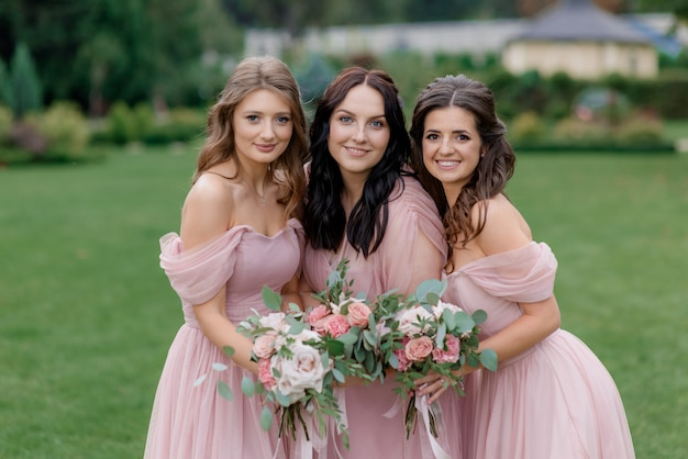 Aantrekkelijke bruidsmeisjes gekleed in lichtroze modieuze jurken met zachte boeketten gemaakt van roze rozen glimlachen
