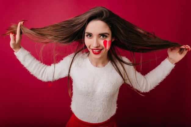Aantrekkelijke bruinharige vrouw in witte trui genieten van fotoshoot in valentijnsdag