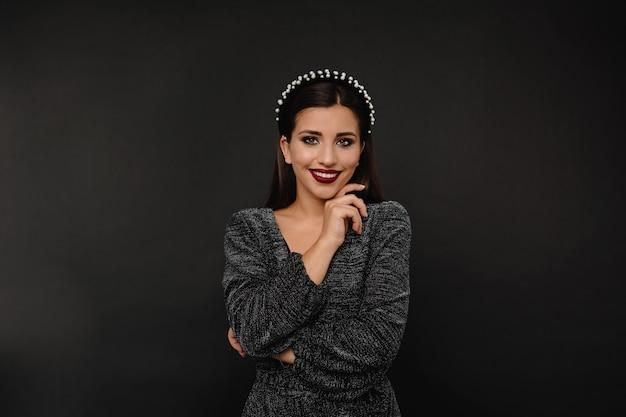 Aantrekkelijke bruinogige vrouw met donkere lippen in glanzende jurk met accessoires in het hoofd