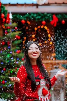 Aantrekkelijke brunette aziatische vrouw in rode kerstmissweater en het rode boog stellen