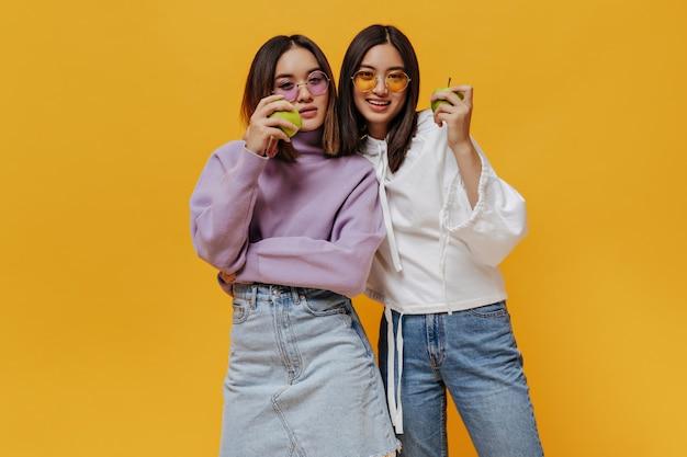 Aantrekkelijke brunette aziatische vrouwen in denim-outfits en sweatshirts kijken naar voren en houden verse smakelijke groene appels op een oranje geïsoleerde muur