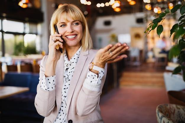 Aantrekkelijke brunette collega zakenvrouw praten op mobiele telefoon met client
