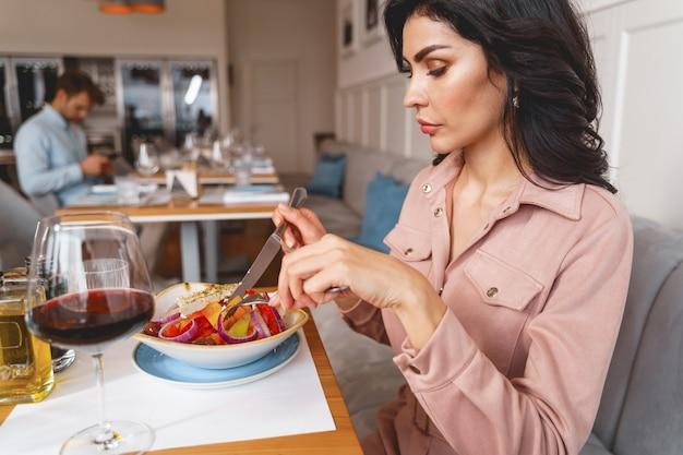 Aantrekkelijke brunette dame die verse salade eet terwijl ze aan tafel zit met eten en wijn