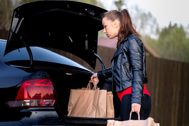 Aantrekkelijke brunette gekleed terloops nemen recyclebare papieren zakken uit de kofferbak van een zwarte auto