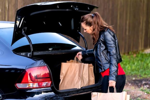 Aantrekkelijke brunette gekleed terloops trekt recyclebare papieren zakken uit kofferbak van zwarte auto