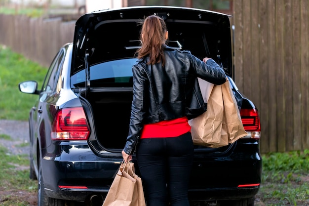 Aantrekkelijke brunette gekleed terloops zet papieren boodschappentassen in zwarte auto kofferbak