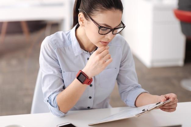 Aantrekkelijke brunette haar kin aanraken met slimme horloges ellebogen op tafel zetten terwijl ze naar beneden kijken