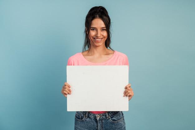 Aantrekkelijke brunette houdt in haar handen een blanco vel papier