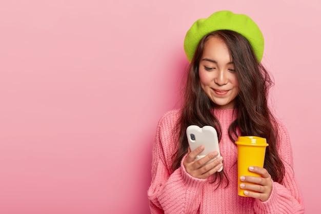 Aantrekkelijke brunette jonge japanse vrouw houdt moderne mobiele telefoon, stuurt tekstberichten in online chat