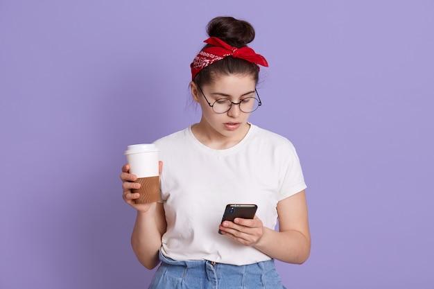 Aantrekkelijke brunette jonge kaukasische vrouw houdt moderne mobiele telefoon en koffie te gaan, stuurt sms-berichten in online chat, draagt witte casual t-shirt en rode haarband