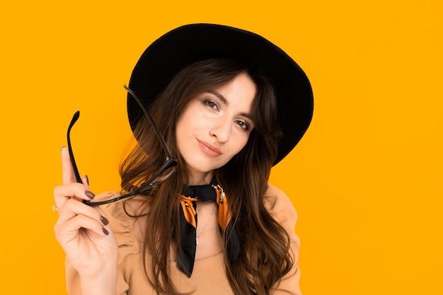 Aantrekkelijke brunette jonge vrouw in een zwarte hoed en blouse en met een bril op een gele achtergrond