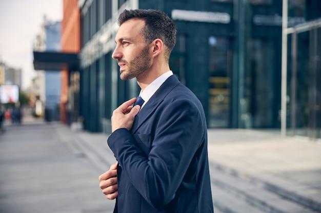 Aantrekkelijke brunette man in officieel pak die kantoor verlaat en denkt terwijl hij zijn das aanraakt Premium Foto