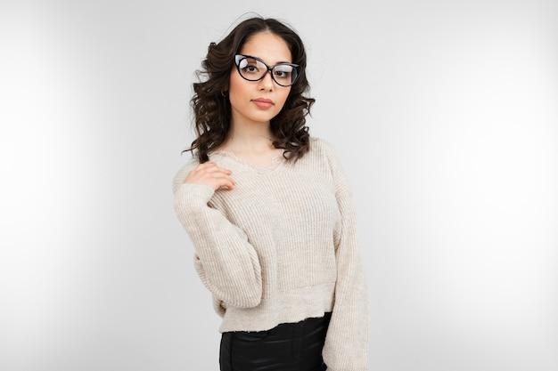 Aantrekkelijke brunette meisje in een stijlvolle bril voor visie vormt op een grijze achtergrond met kopie ruimte.