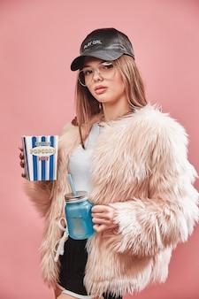 Aantrekkelijke brunette meisje in faux roze bont met popcorn en drank in handen dragen in zwarte sho...