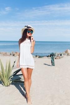Aantrekkelijke brunette meisje met lang haar loopt op het strand in de buurt van zee. ze kijkt ver weg.