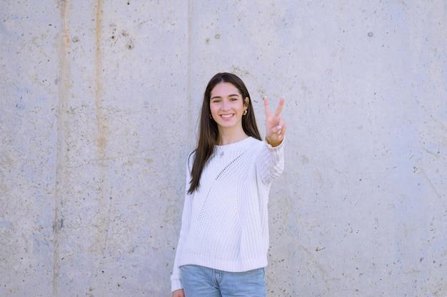 Aantrekkelijke brunette met een gelukkige glimlach die een witte sweater draagt die het vredesteken toont