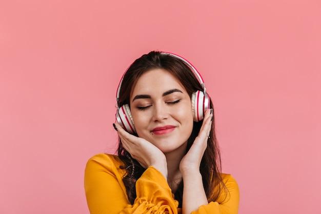 Aantrekkelijke brunette met glimlach en gesloten ogen luisteren naar lied in koptelefoon. dame in felgele blouse poseren op geïsoleerde muur.