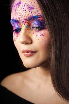 Aantrekkelijke brunette met heldere kunst make-up. gekleurde smokey eyes en blauwe wenkbrauwen.