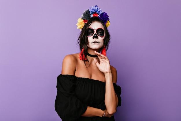 Aantrekkelijke brunette met mexicaans masker vormt in halloween-outfit. vrouw in zwarte jurk vol vertrouwen