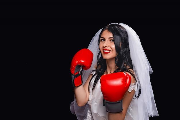 Aantrekkelijke brunette met rode lippenstift, in trouwjurk, sluier en bokshandschoenen.