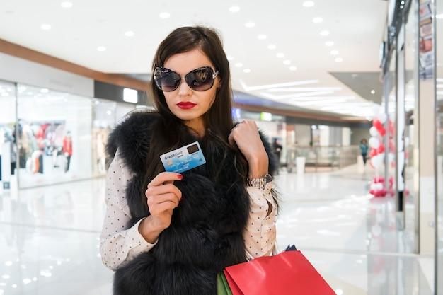 Aantrekkelijke brunette met veel boodschappentassen na het uitgeven van kredietgeld op de achtergrond van het winkelcentrum. dame met een bril en rode lippen die staat en naar de creditcard kijkt na aankoop in de winkel.