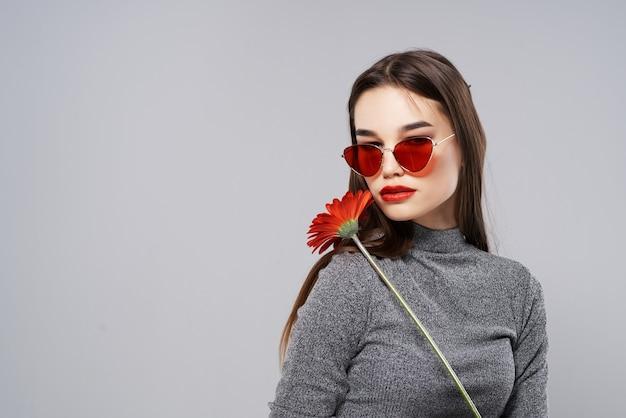 Aantrekkelijke brunette met zonnebril rode bloem romantiek make-up
