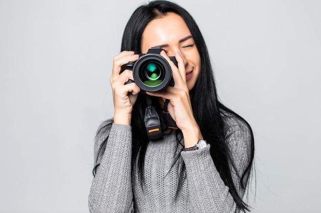 Aantrekkelijke brunette richt haar camera. het samenstellen van een foto in de studio, geïsoleerd op grijze muur