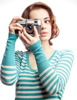 Aantrekkelijke brunette streeft haar camera, geïsoleerd op wit