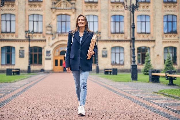 Aantrekkelijke brunette student met mappen en tas achter haar rug naar huis gaan na haar studie aan de universiteit
