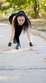 Aantrekkelijke brunette vrouw atleet in de uitgangspositie gehurkt wachten om te draaien in een race of wedstrijd