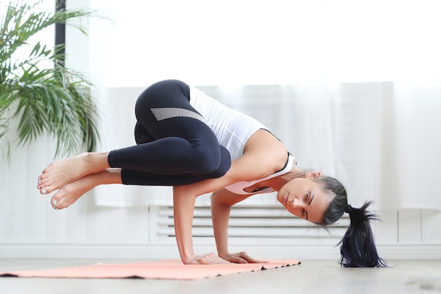 Aantrekkelijke brunette vrouw doet yoga thuis.