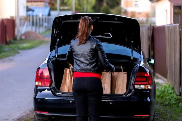 Aantrekkelijke brunette vrouw gekleed terloops trekt recyclebare papieren zakken uit kofferbak van zwarte auto