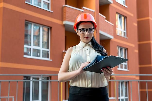 Aantrekkelijke brunette vrouw iets op bouwplaats te berekenen