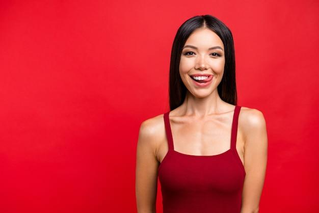 Aantrekkelijke brunette vrouw in een rode jurk poseren tegen de rode muur