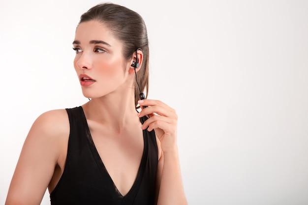 Aantrekkelijke brunette vrouw in joggen zwarte top luisteren naar muziek op oortelefoons poseren geïsoleerd op witte achtergrond paardenstaart kapsel