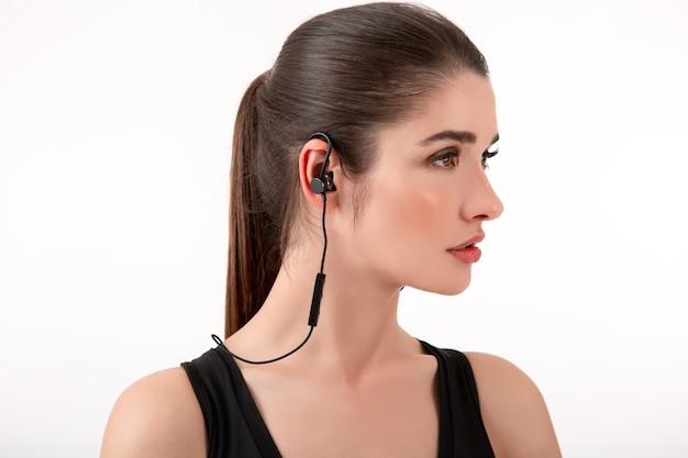 Aantrekkelijke brunette vrouw in joggen zwarte top luisteren naar muziek op oortelefoons poseren geïsoleerd op witte muur paardenstaart kapsel