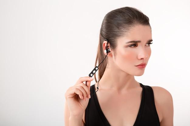 Aantrekkelijke brunette vrouw in jogging zwarte top luisteren naar muziek op koptelefoon poseren