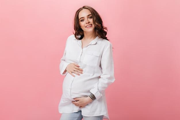 Aantrekkelijke brunette vrouw in wit overhemd en spijkerbroek glimlacht en raakt buik. zwanger meisje in spijkerbroek met zich meebrengt op roze achtergrond.
