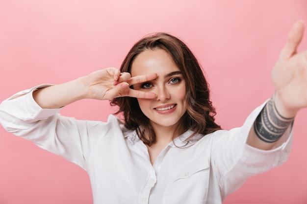 Aantrekkelijke brunette vrouw in wit overhemd neemt selfie en toont vredesteken. gelukkig meisje glimlacht wijd op roze geïsoleerde achtergrond.