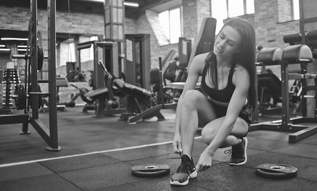 Aantrekkelijke brunette vrouw koppelverkoop schoenveter sneakers in de sportschool.